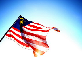 malaysia flag flying in blue sky