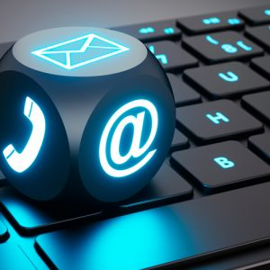lighted computer keyboard with a lighted die showing email and phone icons