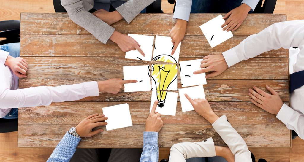 close up of business team with light bulb puzzle